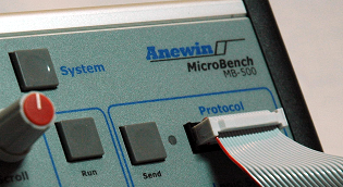 MicroBench MB-500 Instrument front panel showing System button and connected protocol probe